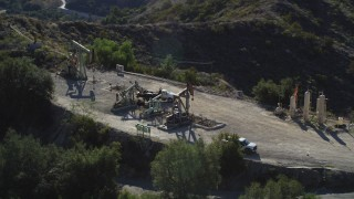 DFKSF01_018 - 5K stock footage aerial video of orbiting around working oil rigs on a hilltop, Santa Paula, California