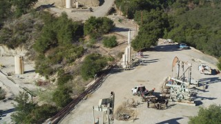 DFKSF01_019 - 5K stock footage aerial video of circling oil rigs drilling on a hilltop, Santa Paula, California