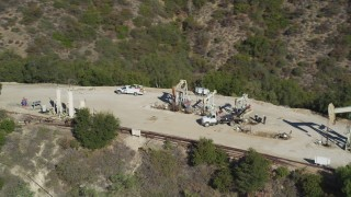 DFKSF01_020 - 5K stock footage aerial video of flying away from four oil rigs drilling on a hilltop, Santa Paula, California