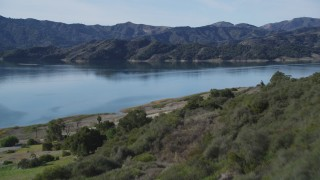 DFKSF01_027 - 5K stock footage aerial video of flying over a wooded hillside, revealing Lake Casitas, California