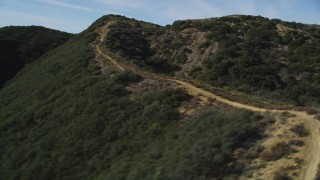 DFKSF01_034 - 5K stock footage aerial video of flying by dirt road on a mountain ridge, Santa Ynez Mountains, California