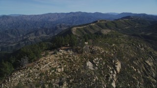 DFKSF01_044 - 5K stock footage aerial video approach and orbit tree-lined slopes, reveal radio tower, Santa Ynez Mountains, California