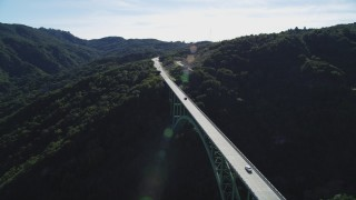 DFKSF01_052 - 5K stock footage aerial video track black SUV crossing Cold Springs Canyon Arch Bridge, Santa Ynez Mountains, California