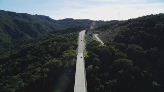 DFKSF01_053 - 5K stock footage aerial video track a white sedan following black SUV on Cold Springs Canyon Arch Bridge, Santa Ynez Mountains, California