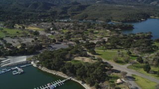 DFKSF01_058 - 5K stock footage aerial video of approaching an RV Park with boats at the docks, Lake Cachuma, California