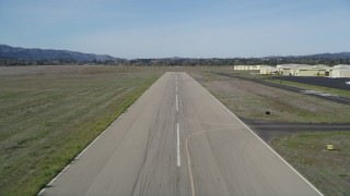 DFKSF01_065 - 5K stock footage aerial video tilt from vineyard to reveal runway, approach for landing, Santa Ynez Airport, California