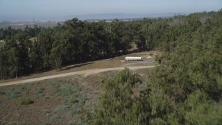DFKSF02_014 - 5K stock footage aerial video of approaching and flying over the edge of a small forest, Nipomo, California