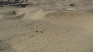 DFKSF02_020 - 5K stock footage aerial video of flying by ATV riders and sand dunes, Pismo Dunes, California