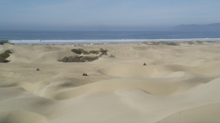DFKSF02_028 - 5K stock footage aerial video of orbiting ATV riders on coastal sand dunes, Pismo Dunes, California
