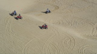 DFKSF02_029 - 5K stock footage aerial video orbiting ATV riders on the sand dunes, Pismo Dunes, California