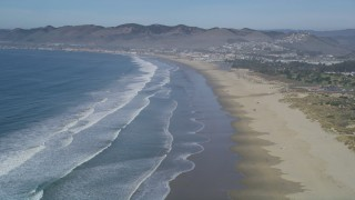 DFKSF02_033 - 5K aerial stock footage video of flying over a beach with waves rolling in, Pismo Beach, California