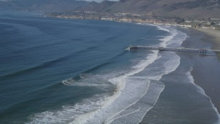 DFKSF02_035 - 5K stock footage aerial video pan across beach, revealing pier and coastal neighborhoods, Pismo Beach, California