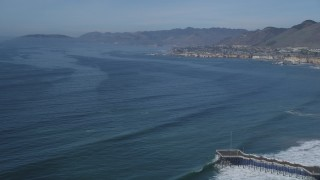 DFKSF02_036 - 5K stock footage aerial video of coastal homes, tilt to bird's eye of pier, Pismo Beach, California
