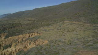 DFKSF02_056 - 5K stock footage aerial video of flying by a dirt road along the coast, Avila Beach, California