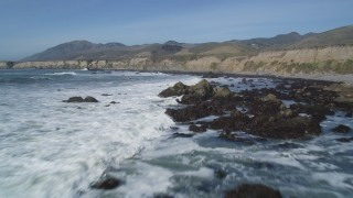 DFKSF02_060 - 5K stock footage aerial video of flying over waves rolling into rock formations, coastal cliffs, Avila Beach, California