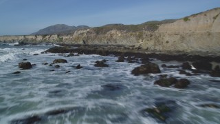 DFKSF02_061 - 5K stock footage aerial video fly over waves rolling into rock formations, coastal cliffs, Avila Beach, California
