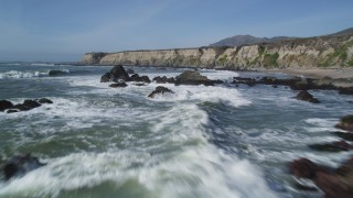 DFKSF02_062 - 5K stock footage aerial video of flying over waves rolling into rock formations, coastal cliffs, Avila Beach, California