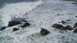 DFKSF02_063 - 5K stock footage aerial video of flying over waves rolling into rock formations, Avila Beach, California