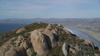 DFKSF03_001 - 5K stock footage aerial video tilt from bay, reveal Morro Rock, Morro Strand State Beach, Morro Bay, California