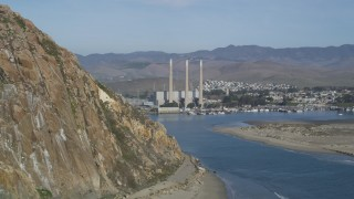 DFKSF03_002 - 5K stock footage aerial video of flying by the Dynegy Power Plant, eclipsed by Morro Rock, Morro Bay, California