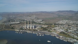 DFKSF03_007 - 5K stock footage aerial video of a beach, coastal homes by the harbor, pan to reveal Dynegy Power Plant, Morro Bay, California