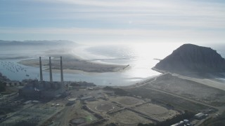 DFKSF03_011 - 5K stock footage aerial video of flying by Dynegy Power Plant and smoke stacks, Morro Rock, and the coast, Morro Bay, California