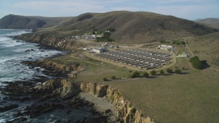 DFKSF03_017 - 5K stock footage aerial video of flying by a coastal abalone farm, Cayucos, California