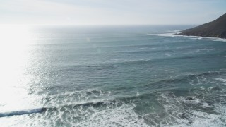 DFKSF03_018 - 5K aerial stock footage video of flying over ocean waves, pan to reveal coastal hills, Cayucos, California