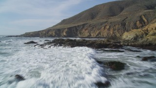 DFKSF03_026 - 5K stock footage aerial video of flying low over waves crashing into coastal cliffs, Harmony, California