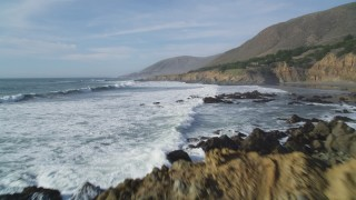 DFKSF03_027 - 5K stock footage aerial video of flying low over waves crashing into rocks along the coast, Harmony, California