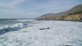 DFKSF03_029 - 5K stock footage aerial video of flying low over waves rolling toward coastal cliffs, Harmony, California