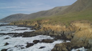 DFKSF03_031 - 5K stock footage aerial video of flying low over rugged coastal cliffs, Harmony, California