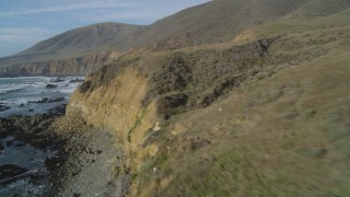 DFKSF03_032 - 5K stock footage aerial video of flying low over rugged coastal cliffs and ocean waves, Cambria, California