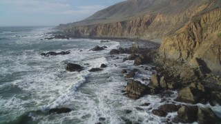 DFKSF03_033 - 5K stock footage aerial video of flying by the rugged coastal cliffs and over waves, Cambria, California