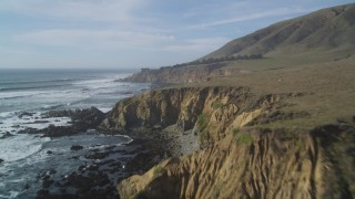 DFKSF03_034 - 5K stock footage aerial video of flying over the jagged coastline's steep cliffs, Cambria, California