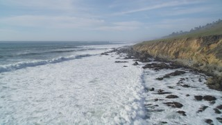 DFKSF03_036 - 5K stock footage aerial video of flying over hills, pan revealing coastal cliffs and ocean waves, Cambria, California