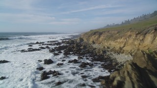 DFKSF03_037 - 5K stock footage aerial video of following the rocky coastline as ocean waves roll in, Cambria, California