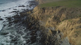 DFKSF03_038 - 5K stock footage aerial video of following the rocky coastline, tilt down to steep coastal cliffs, Cambria, California