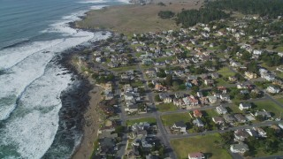 DFKSF03_041 - 5K stock footage aerial video of a bird's eye view of rugged coastal cliffs, tilt to homes near ocean, Cambria, California