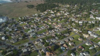 DFKSF03_042 - 5K stock footage aerial video of flying over homes on the coast, Cambria, California
