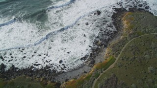 DFKSF03_043 - 5K stock footage aerial video of a bird's eye view of a coastal road and ocean waves, Cambria, California