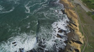 DFKSF03_044 - 5K stock footage aerial video of flying by a beach as waves roll in, Cambria, California