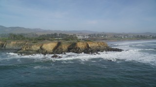 DFKSF03_049 - 5K stock footage aerial video of flying away from jagged coastal cliffs, San Simeon, California