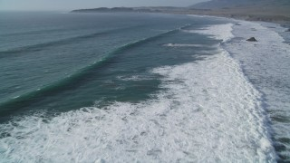 DFKSF03_051 - 5K stock footage aerial video of flying over ocean waves rolling into the coast, San Simeon, California