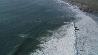 DFKSF03_052 - 5K stock footage aerial video of flying over waves rolling into the coast by Highway 1, San Simeon, California