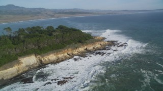 DFKSF03_055 - 5K stock footage aerial video of flying by waves rolling into the coastline, San Simeon, California