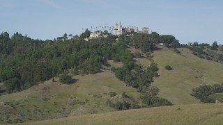 DFKSF03_061 - 5K stock footage aerial video of flying over rocky hillside, revealing iconic Hearst Castle, San Simeon, California