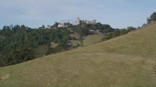 DFKSF03_071 - 5K stock footage aerial video of a wide view of Hearst Castle, eclipsed by a hill, San Simeon, California