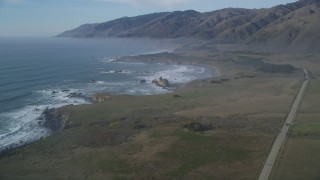 DFKSF03_075 - 5K stock footage aerial video approach the coastline from over Highway 1, San Simeon, California