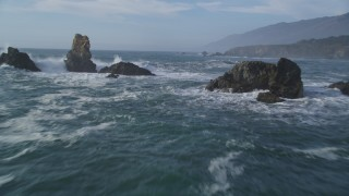 DFKSF03_077 - 5K stock footage aerial video of flying over rock formations and waves off the coast, San Simeon, California